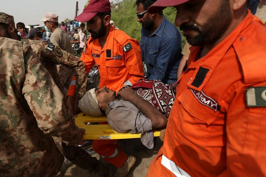 Pakistani security personnel move an injured victim at the site of a train accident in Daharki area of the northern Sindh province, on June 7, 2021.
