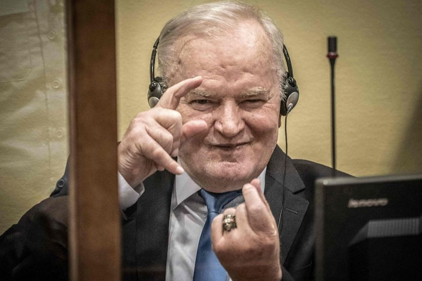 Mladic imitates taking photos as he sits in the defendant box prior to the hearing on June 8, 2021.
