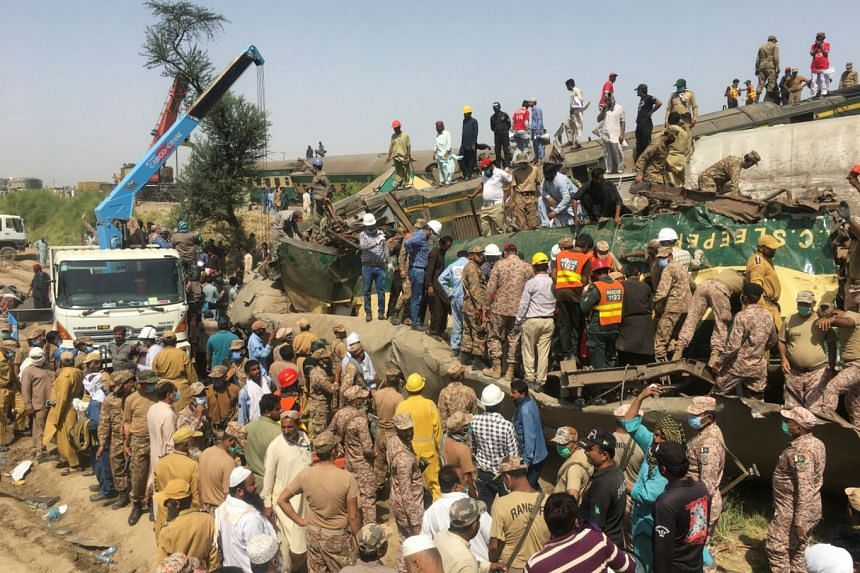Paramilitary soldiers and rescue workers search for victims at the site of a collision between two trains in Ghotki, Pakistan, on June 7, 2021.