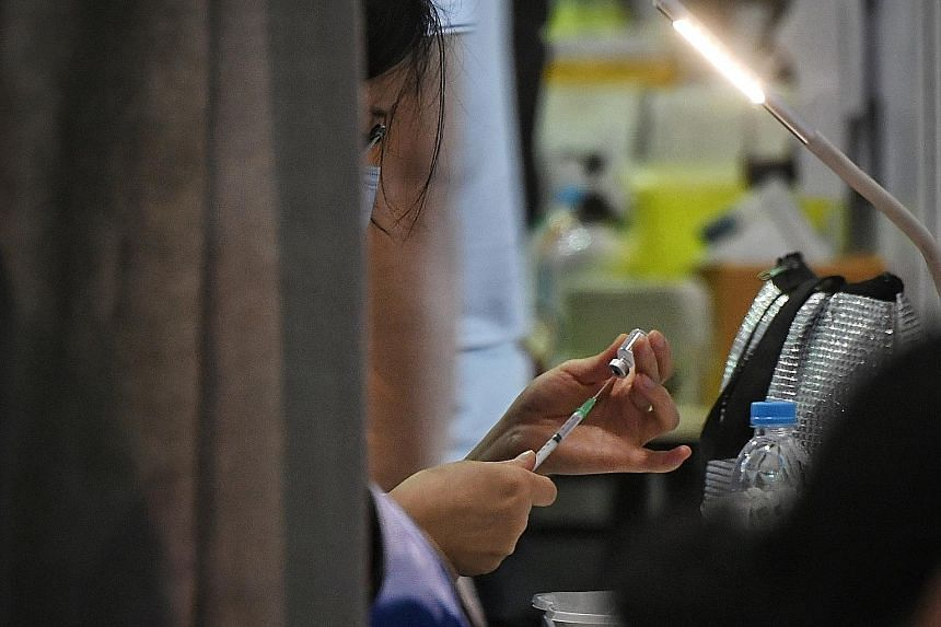 A medical worker drawing a dose of Covid-19 vaccine into a syringe. Booster jabs may be useful when the protective effects of vaccination wane, or if new virus variants are resistant to existing vaccines. ST PHOTO: KUA CHEE SIONG
