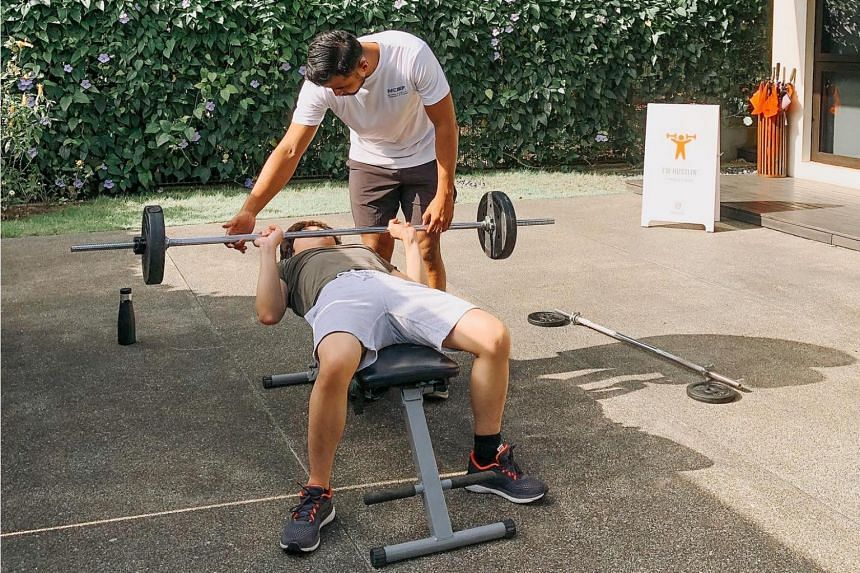 Mobile gym Hustle Hut co-founder Alexander Loo coaching a client.