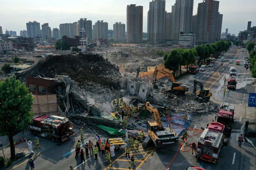 South Korean firefighters search for passengers trapped by the debris of a collapsed building in Gwangju, South Korea, on June 9, 2021.
