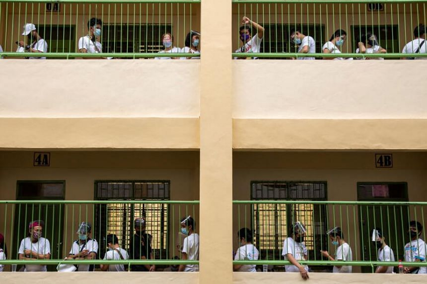 Residents, whose jobs or livelihoods were affected by stricter restrictions imposed amid rising coronavirus disease cases, queue to receive cash assistance from the government, at an elementary school in Quezon City, Metro Manila, Philippines on Apri