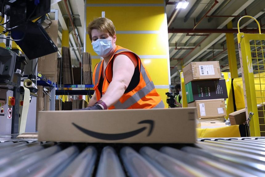An employee prepares a package for shipment at an Amazon logistics centre in Germany.