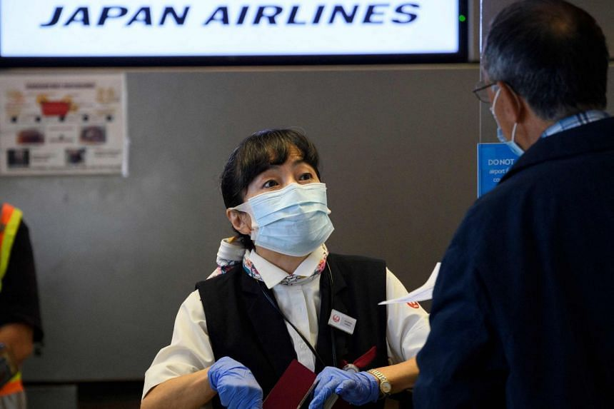 A November 2020 photo shows a Japan Airlines agent checking in a passenger at Los Angeles International Airport in California.
