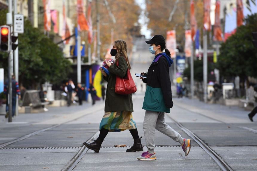 People wearing masks cross an almost empty shopping street in Melbourne on May 26, 2021.
