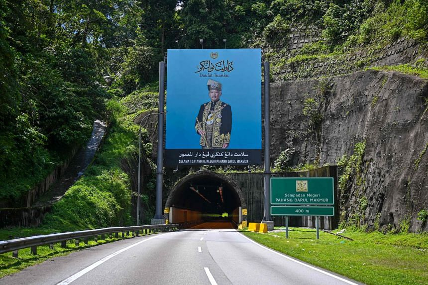 A portrait of Malaysia's King, Sultan Abdullah Ahmad Shah, above a road leading to his home state of Pahang. The ruler appears to have heard his subjects and has taken the rare step of summoning the leaders of all major political parties for audience