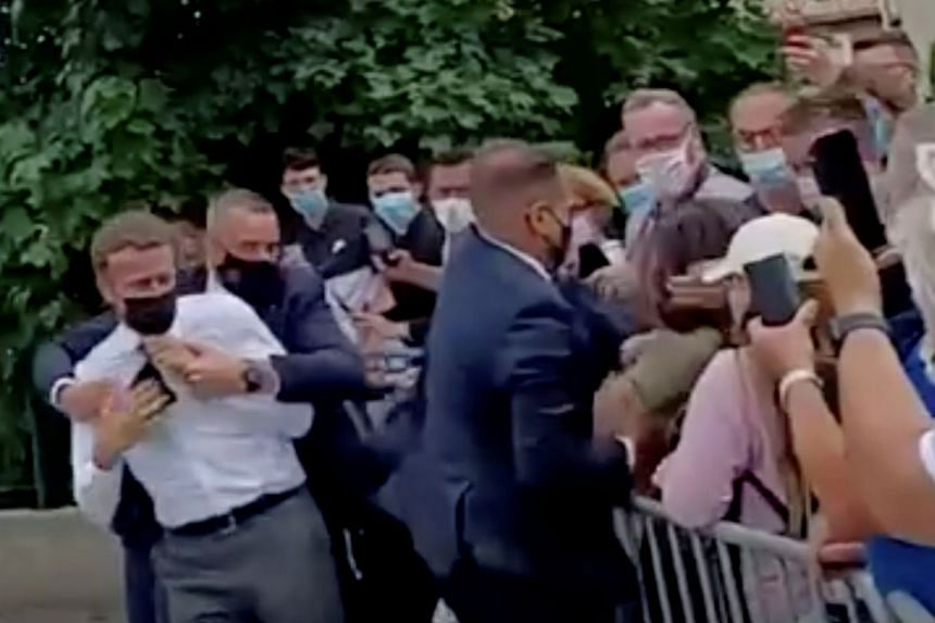 French President Emmanuel Macron is protected by a member of his security staff after getting slapped by a member of the public on June 8, 2021.