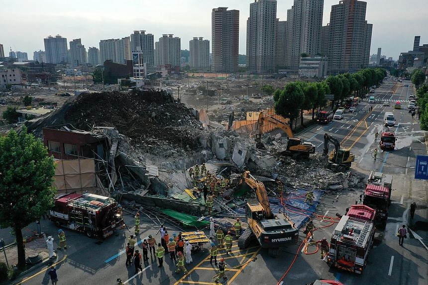Firefighters carrying out rescue operations after a five-storey building collapsed, burying a bus with passengers in the city of Gwangju, South Korea, yesterday.