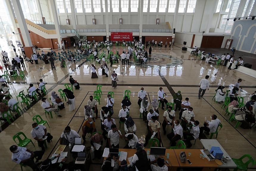 People waiting to be vaccinated at Banda Aceh, Indonesia, yesterday. The country seeks to inoculate more than 180 million, out of its 270 million population, by March next year to reach herd immunity. PHOTO: EPA-EFE