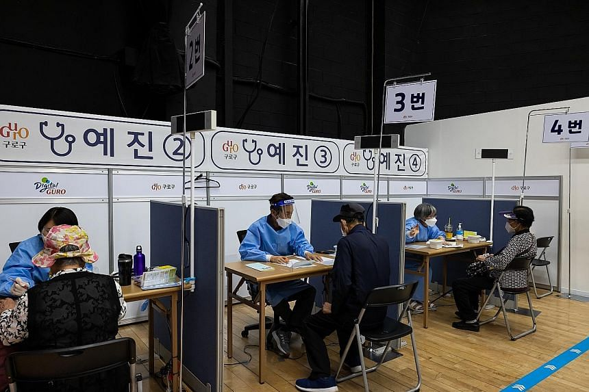Elderly residents speaking with doctors before receiving a dose of the Pfizer-BioNTech Covid-19 vaccine at a vaccination site at Guro Arts Valley Theatre in Seoul's Guro district. Only 4.5 per cent of South Korea's population, or 2.32 million people,
