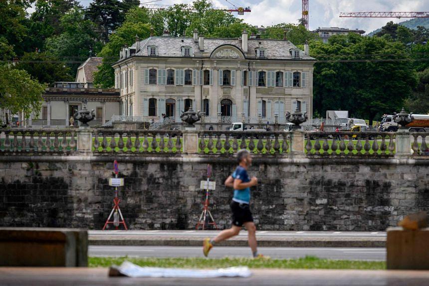 """A man joggs by the """"Villa La Grange"""" in Geneva on June 8, 2021."""