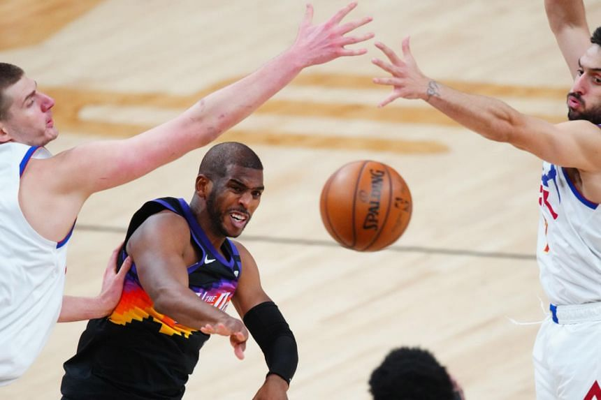 Phoenix Suns guard Chris Paul (centre) passes the ball against the Denver Nuggets at Phoenix Suns Arena in Phoenix, Arizona, on June 9, 2021.