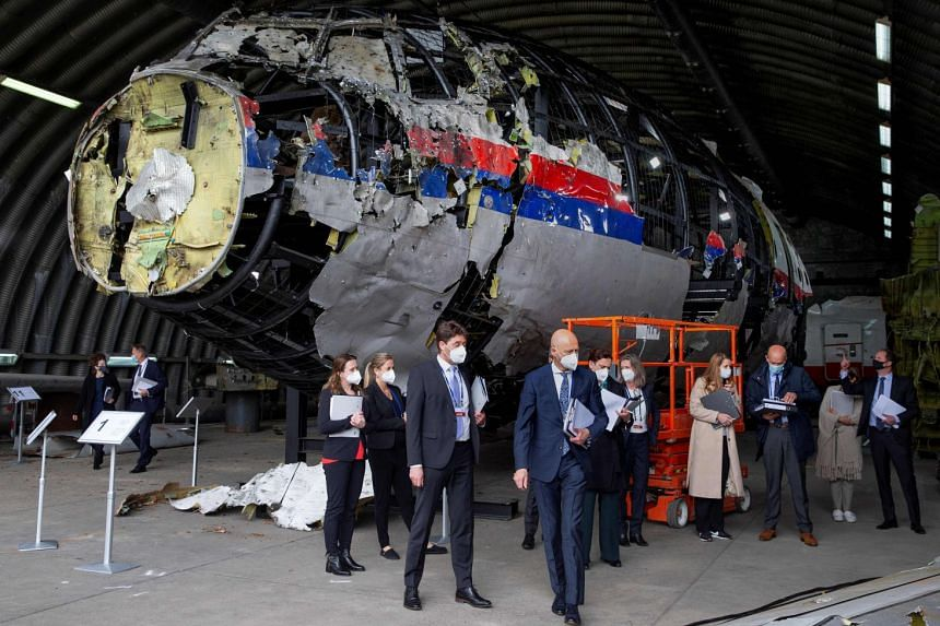 Presiding judge Hendrik Steenhuis (centre), other trial judges and lawyers view the reconstructed wreckage of flight MH17 in May 2021.