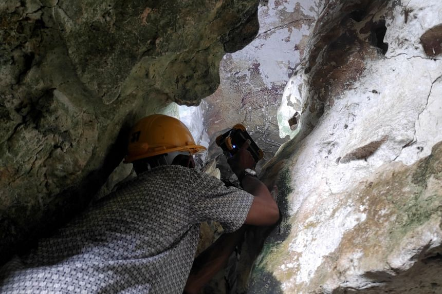 An archeologist inspects the world's oldest limestone cave painting in Maros, Sulawesi, on May 27, 2021.