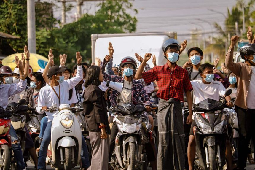 A photo taken on May 18, 2021, showing protesters in Mandalay making the three-finger salute during a demonstration against the military coup.