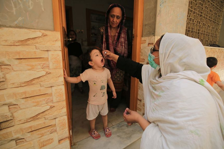 A health worker administers a polio vaccine to children in Peshawar, Pakistan, on June 7, 2021.