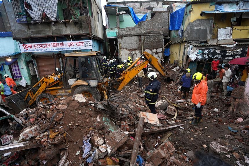 Rescue workers remove debris to search for survivors after a residential building collapsed on top of another building in Mumbai, on June 10, 2021.