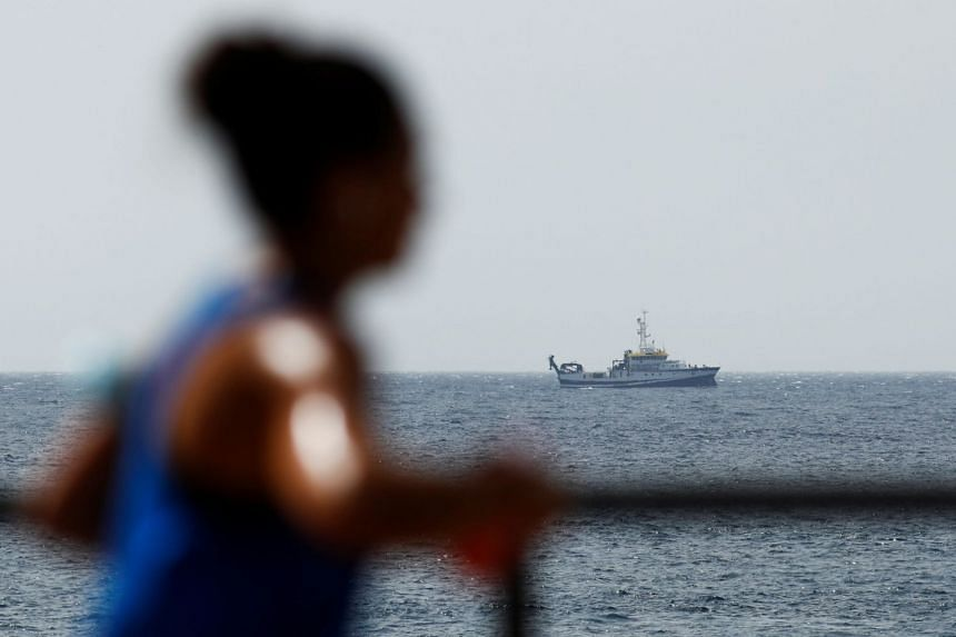 A woman exercises on the Tenerife coast as authorities carry out a sea search for the second missing child and her father. on June 11, 2021.