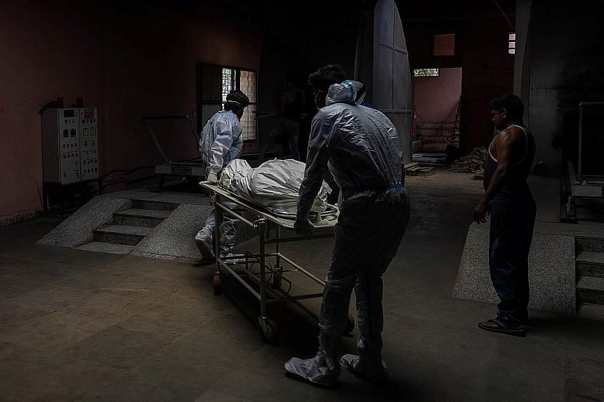The body of a Covid-19 victim being moved to a crematorium in New Delhi yesterday. Concerns around under-reporting of deaths in India were heightened during the second wave in the past two months as crematoriums overflowed with bodies of Covid-19 vic