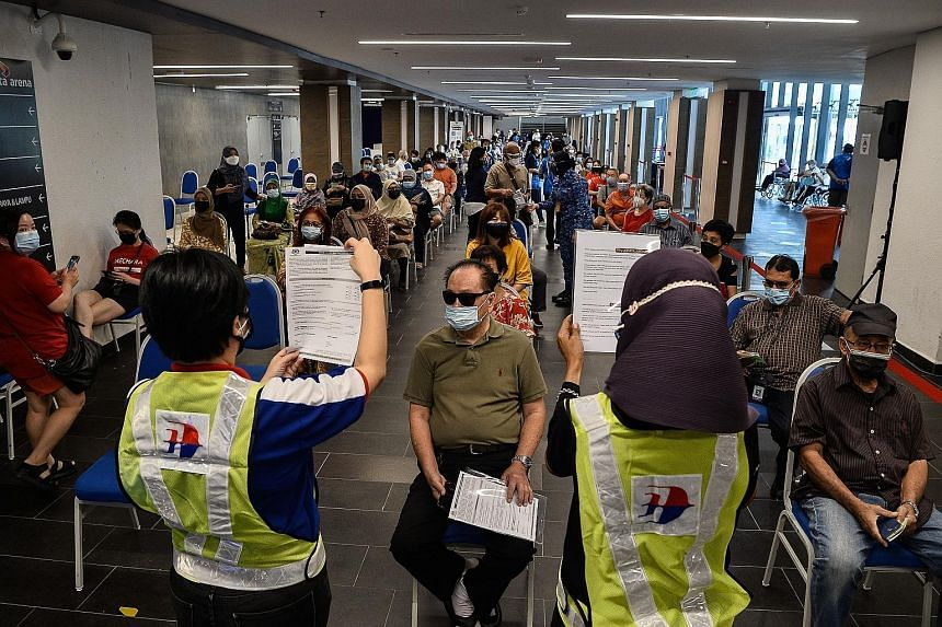 People waiting to receive Covid-19 vaccine shots at the Axiata Arena Vaccine Centre in Bukit Jalil yesterday. The Malaysian government is speeding up the pace of vaccination in order to reach herd immunity by year end. PHOTO: BERNAMA