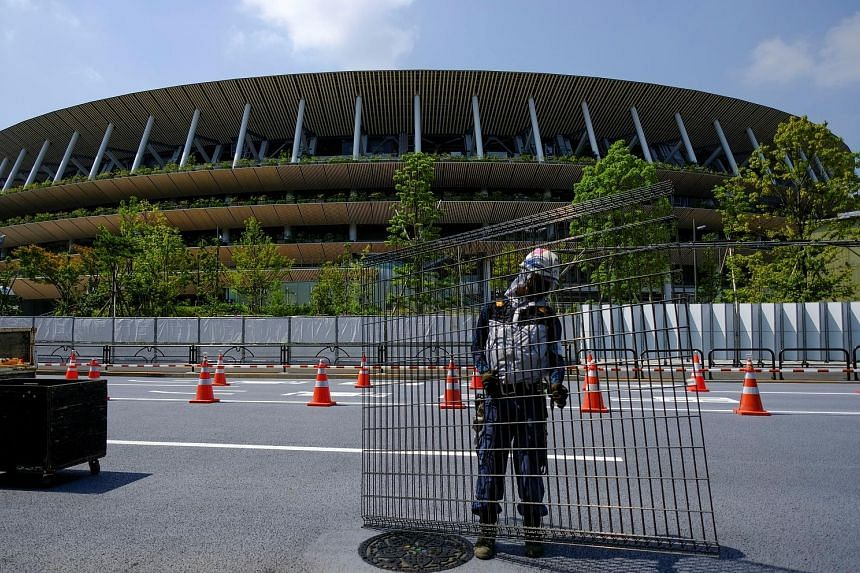 A worker setting up a security fence outside the Tokyo Olympic Stadium yesterday. Experts are now zeroing in on domestic factors that could contribute to an uptick in cases that would coincide with the Games. PHOTO: REUTERS