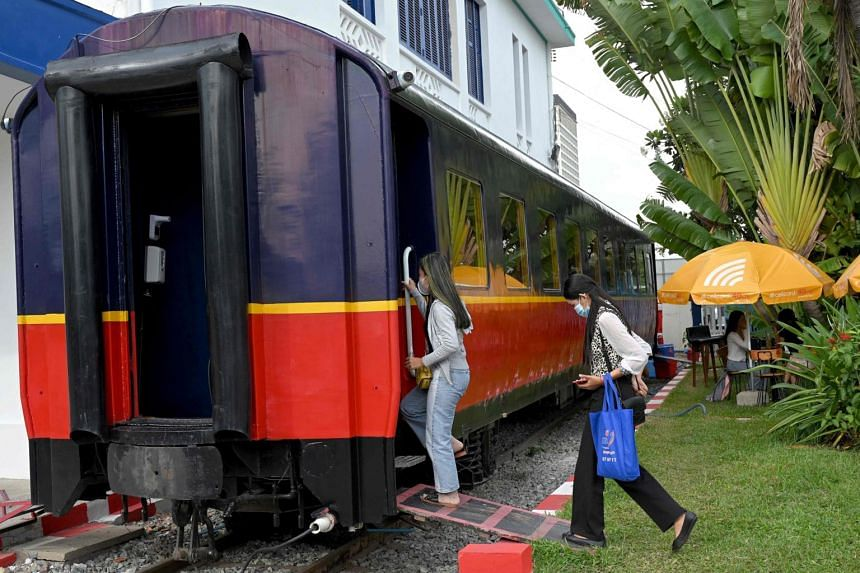Women walking into a train carriage that has been converted into a cafe at a railway station in Phnom Penh on June 5, 2021.