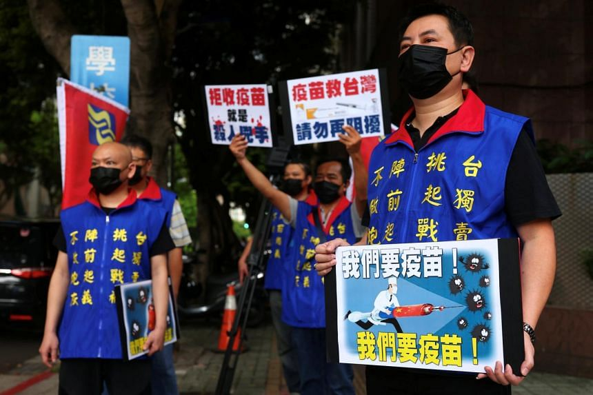 People hold placards calling for the Taiwanese government to allow the use of Chinese Covid-19 vaccines on May 24, 2021.