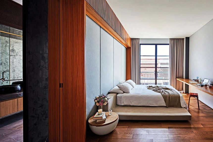 A perforated metal sliding door screens off the master suite's sleeping area from the walk-in wardrobe and bathroom.