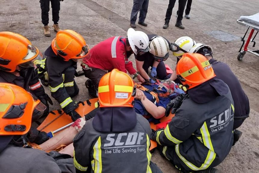 SCDF officers treating the injuries of the worker who fell while unloading steel pipes on board a vessel in Jurong Port, on June 10, 2021.