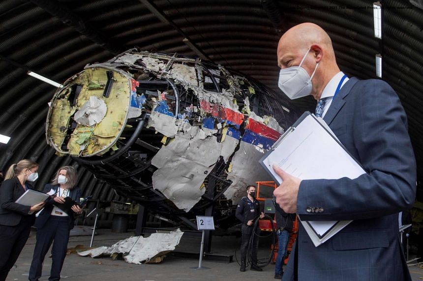 Presiding judge Hendrik Steenhuis (right), plus other trial judges and lawyers, view the reconstructed wreckage of Malaysia Airlines Flight MH17.