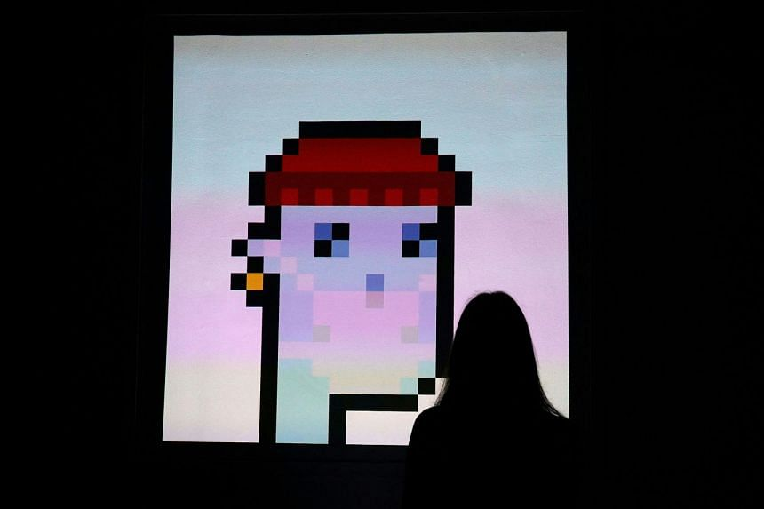 """A woman looks at """"CryptoPunk 7523"""" by Larva Labs during a media preview on June 4, 2021."""