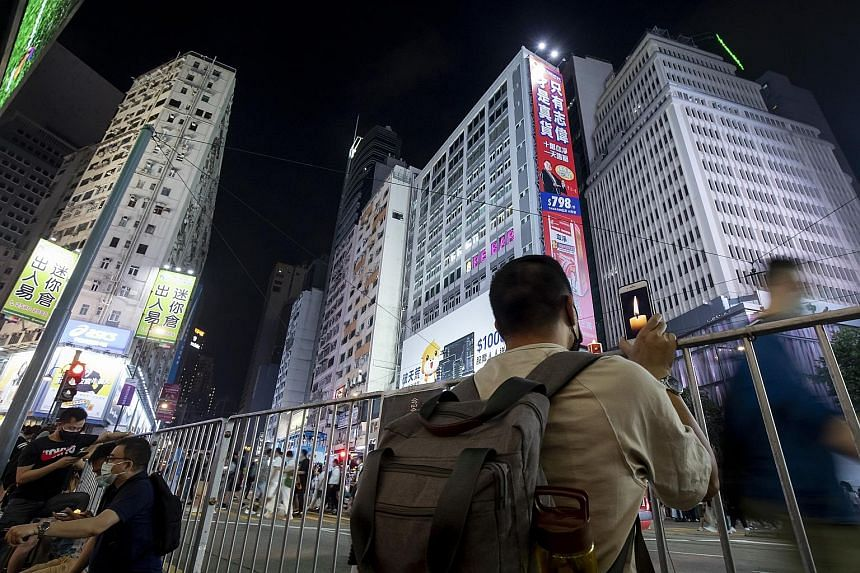 Above: Mr Hanscom Smith, the US Consul-General in Hong Kong, has criticised the city's national security law. Left: A man with a phone showing a lighted candle near Victoria Park, the site of the annual Tiananmen vigil in Hong Kong, on June 4. Critic