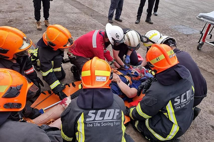 The stretcher carrying the injured worker being manoeuvred through a narrow hatch. The worker fell while unloading steel pipes on board a vessel at Jurong Port on Thursday. Right: SCDF officers treating the worker.