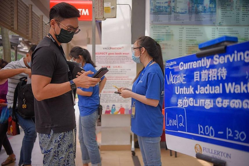 People waiting to enter the Buona Vista Community Club yesterday to receive their Moderna jab.