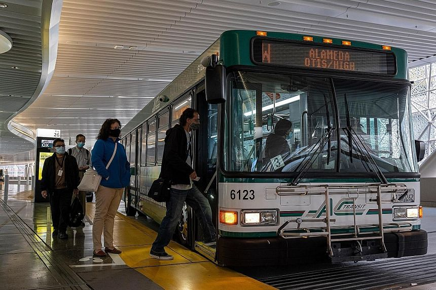 Commuters wearing masks boarding a bus in San Francisco, California, on Wednesday. The US Centres for Disease Control and Prevention said it will no longer require travellers to wear masks in outdoor transit hubs and in outdoor spaces on ferries, bus