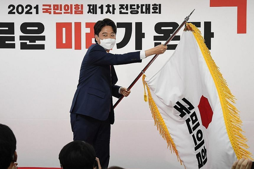 Mr Lee Jun-seok, the new chairman of South Korea's main opposition People Power Party, waving the party's flag at its headquarters in Seoul after his election victory on June 11, 2021.