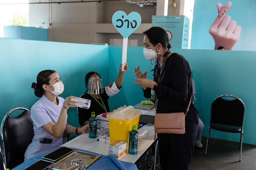 THAILAND: Health workers attending to a woman about to receive a dose of Covid-19 vaccine at an inoculation centre set up at the Central Eastville shopping mall in Bangkok on Monday.