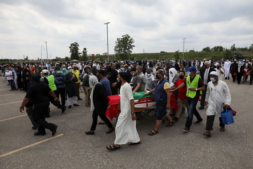 People transport a flag-wrapped coffin, outside the Islamic Centre of Southwest Ontario, during the funeral of the Afzaal family on June 12, 2021.