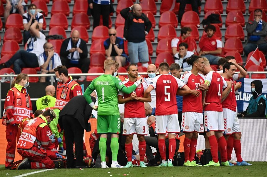 Denmark's players gather as paramedics attend to Christian Eriksen (not seen) in Copenhagen on June 12, 2021.