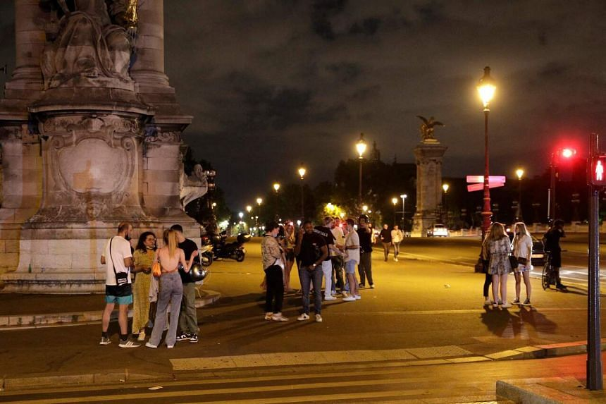 People standing in a street near Les Invalides in Paris, past the 11pm Covid-19 curfew, on Saturday.