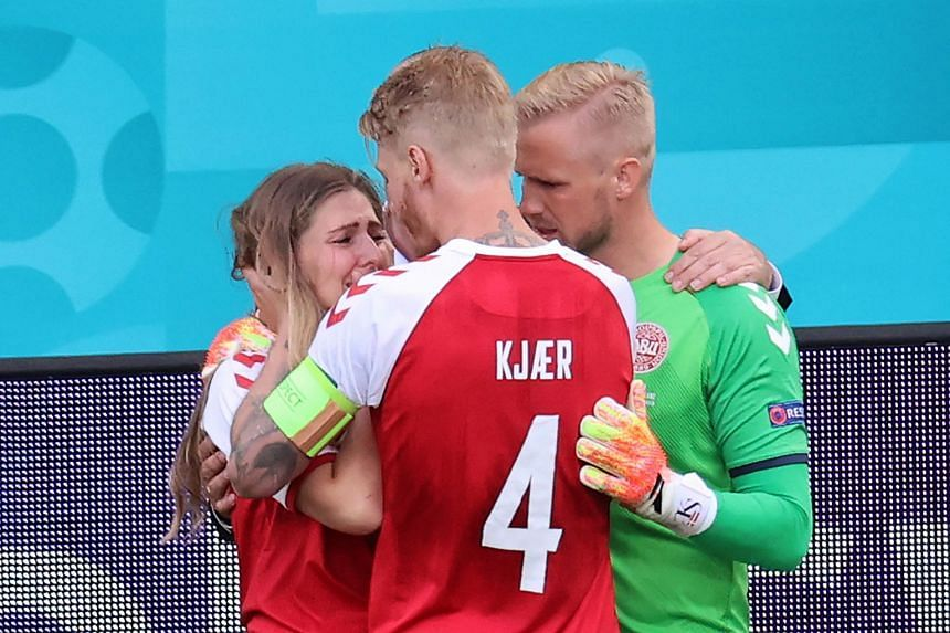 Denmark's goalkeeper Kasper Schmeichel (right) and defender Simon Kjaer (centre) comfort Eriksen's partner, Sabrina Kvist Jensen, after his collapse on the pitch.