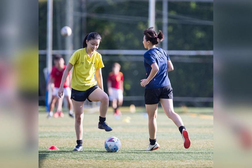 Keeping:Score campaign co-founders Brander Na (left) and Puah Jing Wen playing football.