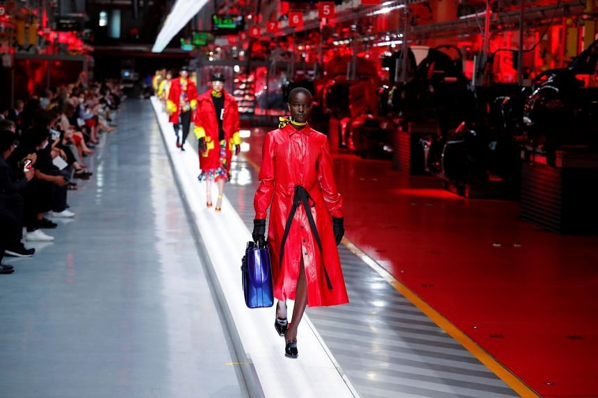 Models present outfits from luxury carmaker Ferrari's first internally-designed fashion collection in Maranello, Italy, on June 13, 2021.