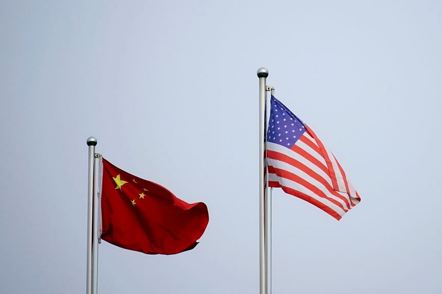 Chinese and US flags flutter outside a company building in Shanghai on April 14, 2021.