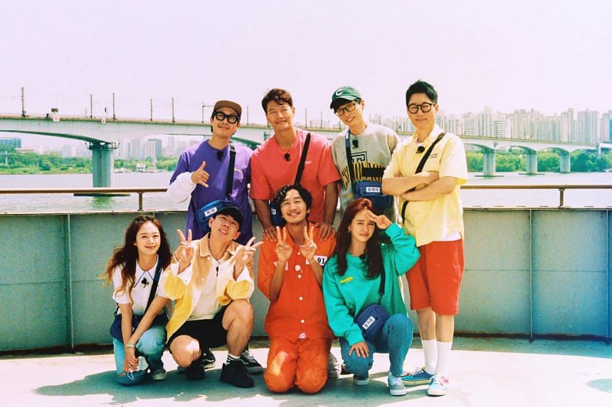 Running Man cast members take a photo with Lee Kwang-Soo (bottom row, in orange) during his final episode for the show.