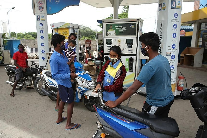Motorcyclists queueing to refill fuel tanks at a petrol station in Bangalore on June 11, 2021.