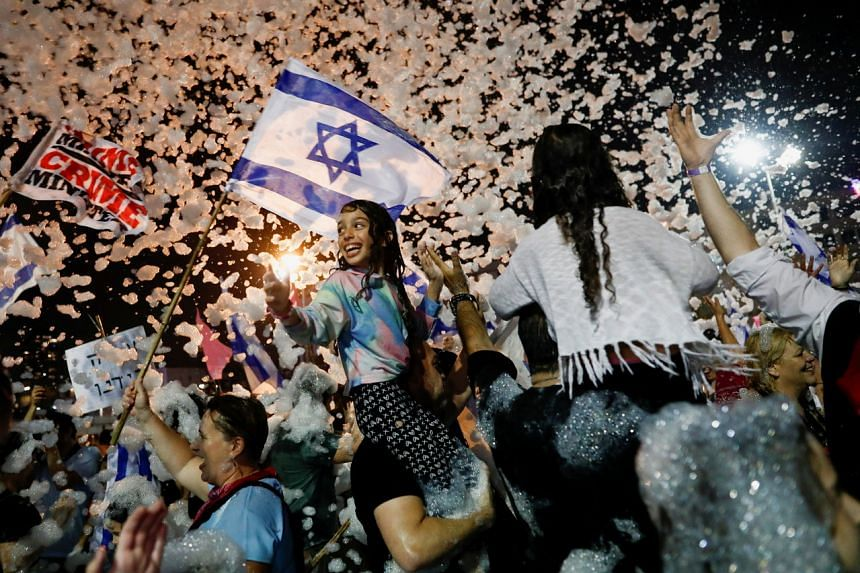 People celebrate after Israel's parliament voted in a new coalition government at Rabin Square in Tel Aviv on June 13, 2021.