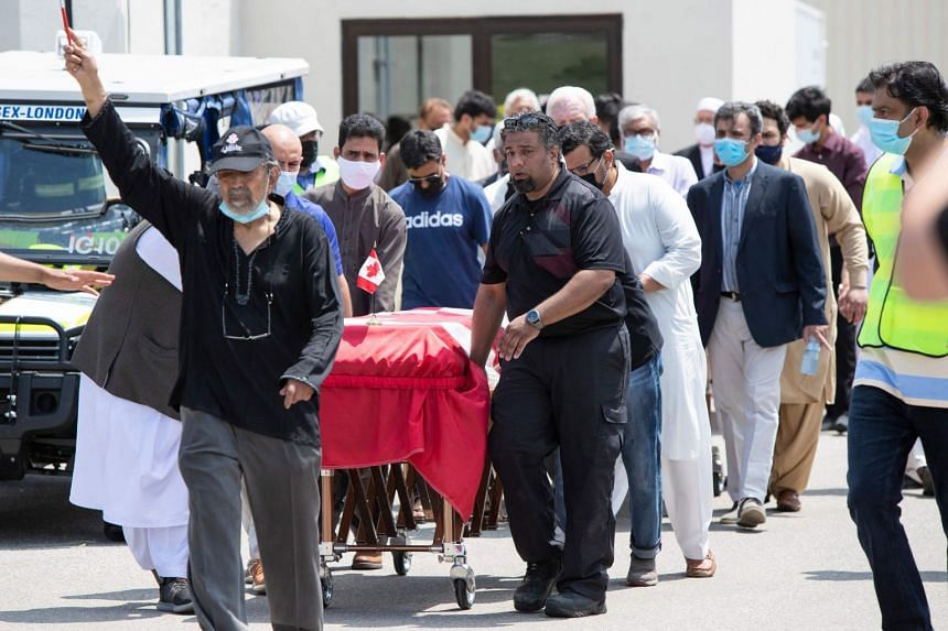 Pallbearers move the caskets of four members of the Afzaal family at the Islamic Centre of Southwest Ontario, on June 12, 2021.