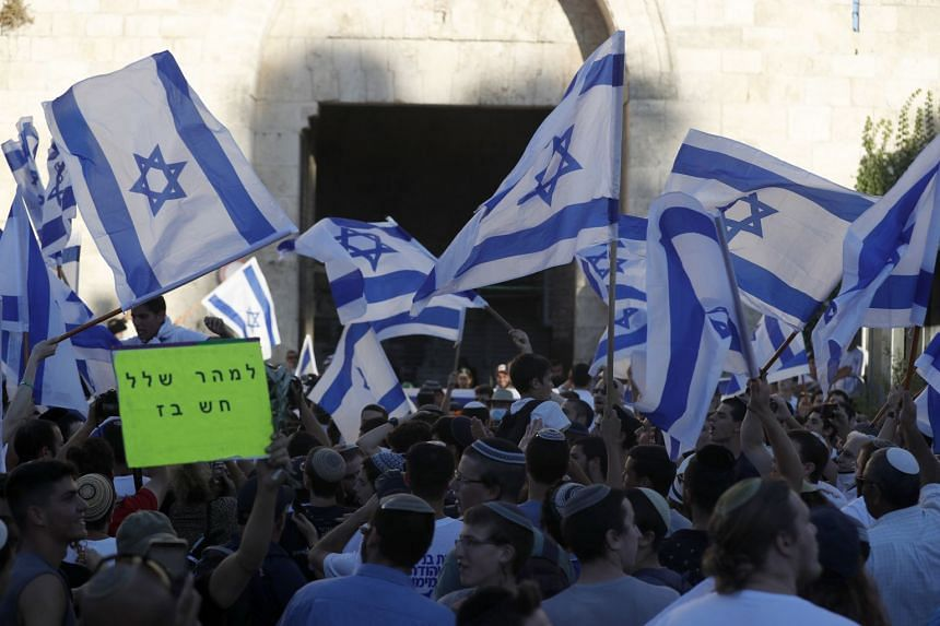 """Members of Israeli right-wing groups take part in a """"Flag March"""" next to the Damascus gate of Jerusalem's Old City, on June 15, 2021."""